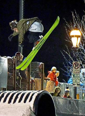 Spectators look on as a skier competes in the Dew Tour streetstyle competition on Washington Avenue in Breckenridge Friday.