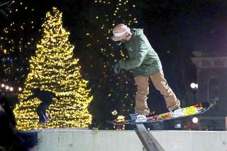 A snowboarder nose presses a rail on the Dew Tour streetstyle course on Washington Avenue in Breckenridge Friday.