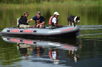 Maui, a 9-year-old Border Collie, and owner Marcia McMahon of Fairplay, join members of Summit County's Water Rescue Team on Tuesday, July 19, during an operation to locate a body at North Pond in Silverthorne.