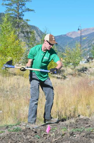 Andy Rohlf swings a pickaxe to break ground for a trail that will help his brother Chris Rohlf become an Eagle Scout.