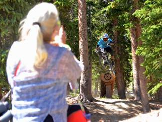 Crested Butte pro Colin Pickett drops off the log jump as his mom, Erin Kennedy of tiny McCoy, Colorado, takes video on her iPhone during Stage Two of the 2016 Keystone Big Mountain Enduro on July 9. The annual event drew more than 300 pro and amateur riders to the Keystone Bike Park for six stages of downhill riding on berms, drops and boulders.