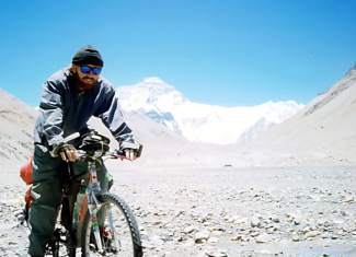 Brian Brill poses on his bike at north Mount Everest base camp in 1998, with the peak looming in the background.
