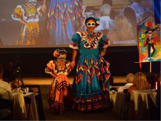 A mother and her daughter donned colorful dresses for the FIRC's fifth annual Fashion Show.