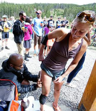 Jeremiah Amaku, left, of the The Steadman Clinic in Vail offers medical attention to Amy Freeman of Breckenridge after Freeman had a run-in with a tree during the 2015 Fall Classic mountain bike race in Breckenridge on Sept. 6. Freeman went on to finish fifth in the women's pro/elite division.