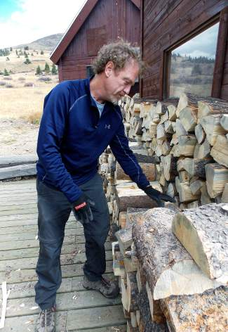 Dillon resident Brian McPike carefully stacks wood outside of Ken's Cabin, one of four huts in the Summit area.