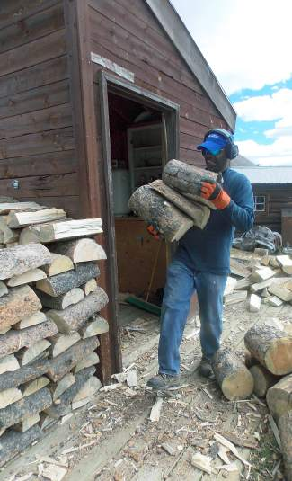 Ken Glenn carries split wood during a volunteer weekend with the Summit Huts Association.