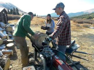 Mike Zobbe, executive director with the Summit Huts Association, shows volunteers Courtney Wilkinson and Paul Swidzinsnki how to work the log splitter at Ken's Cabin, one of four backcountry huts in Summit County.