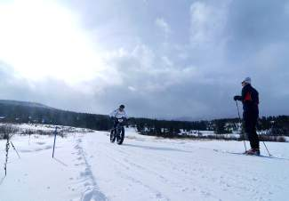 A skier and biker cross pathes at the Gold Run Nordic Center during the inaugural Fat Bike Open in Breckenridge. This season, bikes will be allowed on a select number of groomed trails at the center three days per week.