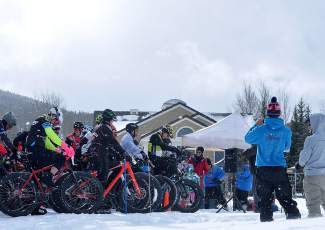 Riders line up at the start as snow begins to fall before the inaugural Fat Bike Open at Gold Run Nordic Center on Dec. 5. The race drew nearly 70 riders from across the state, including several pros.
