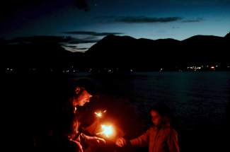 A family lights Roman candles along the shores of Lake Dillon just before the Frisco fireworks show on July 4th.