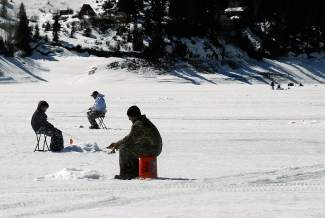 Nine-year-old Kyle Cannon, left, is joined by Chris Trujillo, center, and his father, Ed Cannon, all of Littleton, as they ice fish on Green Mountain Reservoir in 2012. With the snows, expect slushy conditions as the snow weighs down the ice, allowing water onto the surface were the snow insulates it from freezing.