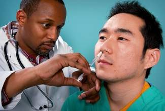 Using a small syringe, a doctor delivers the H1N1 vaccine mist into a patient's right nostril. There are two types of flu vaccine: the flu shot and the nasal spray vaccine.