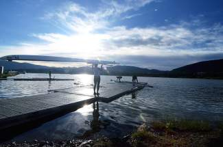 A rower carries a boat to the Frisco Rowing Center dock shortly after sunrise on an August morning. Rowers prefer early-morning sessions, when the water on Lake Dillon is calm and cooperative.