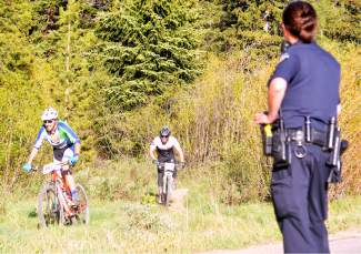 A Breckenridge police officer looks on as two riders jockey for position in final few hundred yards of the Gold Run Rush on June 15. More than 150 junior and adult mountain bikers came to French Gulch for the annual tour of B&B, Minnie Mine and other routes past dredge ponds and mine tails east of downtown Breckenridge.