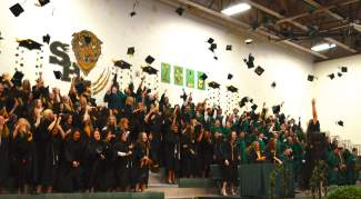 Summit High School graduates tossed their caps in the air at the conclusion of Saturday morning's ceremony.
