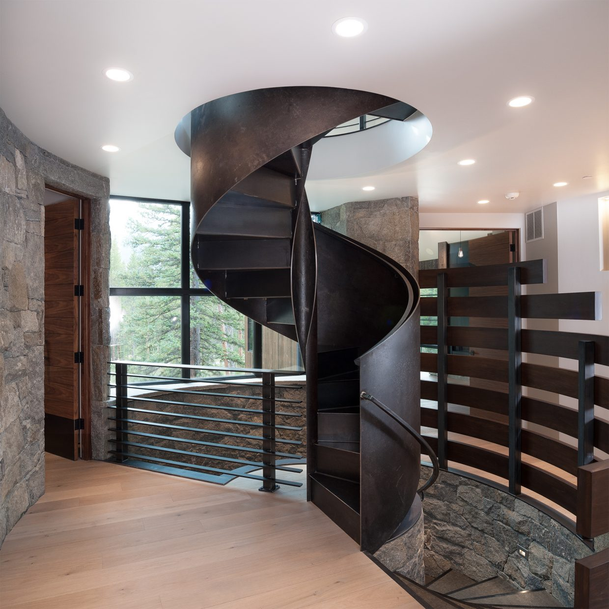 The highlight of the home is a large, steel staircase that was fabricated in Switzerland and craned into the home. Beneath it, a spiraling stone was implemented, based on a French castle. Photo courtesy Geoff Llerena