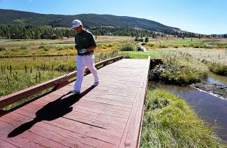Summit High School's Keegan Cancelosi crosses a bridge to tee off on the 18th hole during the Keystone Ranch Invitational Thursday.