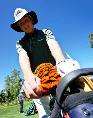 Summit High School's Graham Gaspard places a tiger headcover on his driver after teeing off on the first hole at the Keystone Ranch Invitational Thursday.