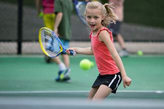 A young camper takes a swing at the ball during tennis camp in Breckenridge. Town tennis coordinator suggests simple warm-ups and stretches for players to ward off injury early in the season.