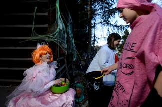 Annie Evans hands out candy on the steps of a Harris Street house in Breckenridge on Friday, October 31. The trick-or-treater on the right dressed as a whoopie cushion. Before poking him, Evans asked him,