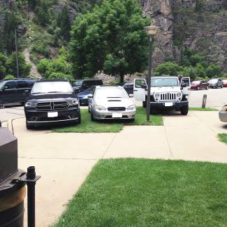 Vehicles parked on grass at the Hanging Lake rest area.