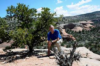 The author crouches beside a pinon pine clinging to the plateau above Rattlesnake Canyon.