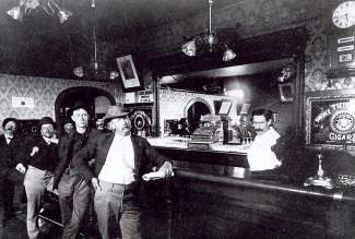 "Located on the southeast corner of Lincoln and Main in Breckenridge after the turn of the century, Weaver Brothers Saloon was one of many in town. Advertising for the saloon noted that the drinks were ""seductive but seldom intoxicating."" Note the ornate ceiling lights, the mirror cigar advertisement and the large mirror behind the bar. The clock showing U.S. Observatory time was updated hourly by Western Union Telegraph."