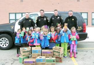 Members of Summit Cove Daisy Scout Troop 979 present 10 boxes of Girl Scout Cookies™ to representatives of the Summit County Sheriff's Office. The cookie donation was done as part of the Girl Scouts of Colorado's Hometown Heroes program.