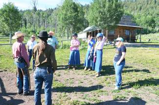 Rusty Spurr Ranch owner Han Smith (far left, red shirt) gives an introductory talk before the cattle drive. Reporter Jessica Smith is on far right.