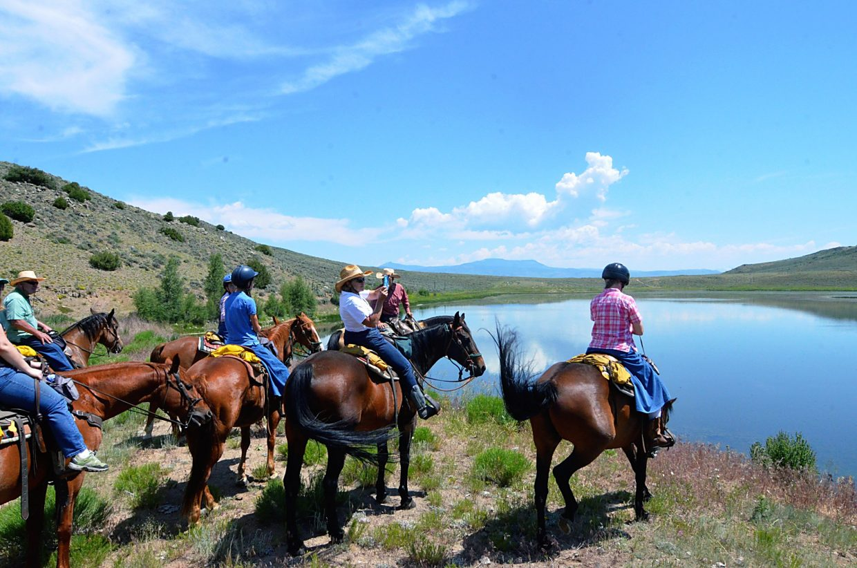 Participants of the cattle drive at Rusty Spurr Ranch take a break to look out over a large pond while the cattle drink and rest.