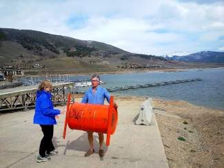 Rotarians Susan Juergensmeier, left, and Lee Edwards carry the device that measured when Dillon Reservoir officially melted away from the Dillon Marina. The Rotary Club of Summit County announced the winners of its 29th annual Ice Melt Contest on Friday, May 21.