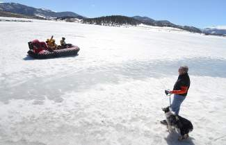 A local looks on as volunteers with Summit County Water Rescue Team take Rotarian Wendy Myers to the middle of Lake Dillon for the annual Dillon Ice Melt device launch in 2015. The device is still on the surface of the lake this season, but experts don't recommend any travel on the lake as ice near the shore begins to fracture.