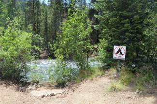 No camping signs remain near stream crossings along Montezuma Road in Keystone.