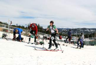 A skier passes by competitors in trainsition from biking to skiing at the 23rd annual Imperial Challenge in Breckenridge. The race returns on April 23 for the 25th season and features a combination of biking, alpine touring and downhill skiing.