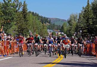 Hundreds of mountain bikers ride south on Main Street in Breckenridge during the start of the Firecracker 50 Mountain Bike Race Monday, July 4, 2016.