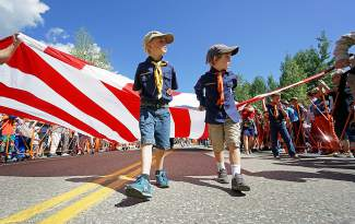 The American flag is carried by Cub Scouts and Boy Scouts down Main Street in Breckenridge during the 2016 4th of July Parade.