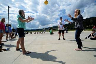 Payton Weinman, left, and Sarah Day, both 14-year-old Summit Cove residents, toss a ball to each other as part of a game Wednesday, Aug. 13, during the Summit High School freshmen orientation event called Jumpstart.