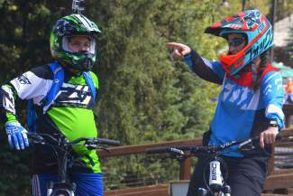 A female instructor with the Keystone Bike Academy gives a student pointers at the base-area skills park before taking a ride to the top of the on-mountain trails. The Keystone Bike Park is home to 56 total downhill trails, all labeled like ski runs with green, blue, black and double-black symbols.