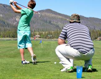 A Keystone Golf Club coach keeps an eye on form while a student hits for driving practice during a PGA Junior League session in June. The league is the first of its kind in Summit County and gives young golfers the chance to practice — then play — in small groups with professional help.