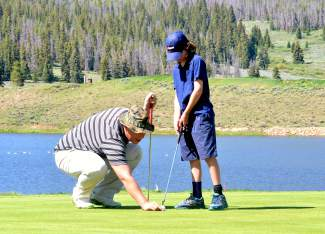 A young golfer gets instruction from a coach during a morning session for the PGA Junior League program at Keystone Golf Club in June. The program combines small-group practice sessions with weekly tournaments to teach new golfers the rules, etiquette and form of the game.