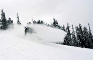A snowboarder gets low to spray fresh snow on opening day at Keystone Nov. 6. The resort received 4 inches of snow overnight and more than 12 inches in 48 hours before the first chair of the season.