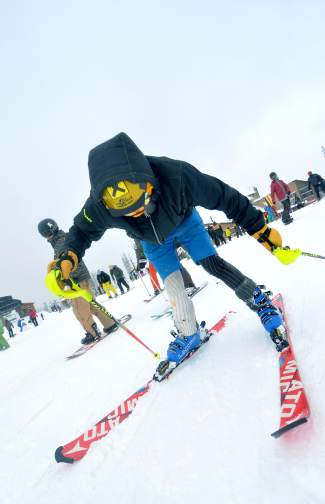 A ski club athlete tightens his bindings near the top of Spring Dipper on Keystone opening day Nov. 6.