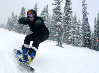 A snowboarder cruises down Spring Dipper on opening day at Keystone Nov. 6. The resort saw several thousand visitors after receiving 4 inches overnight.