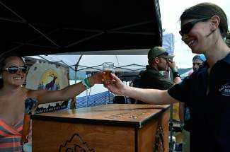 A beer vendor hands over a tasty brew sample to a festival goer at last year's Lake Dillon Brew Fest. This year's event, now in it's fourth year, sold more than 800 tickets, a 30 percent increase over 2013.