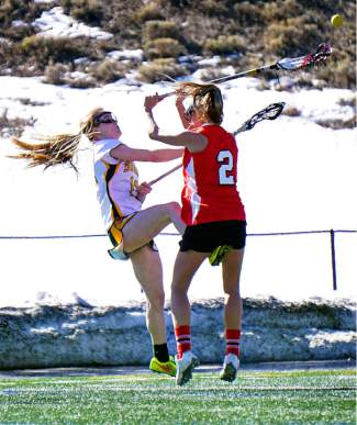Summit's Kenady Nevicosi (13) knocks the ball free from an Aspen player at a home girl's varsity lacrosse game on April 7. The Tigers lost, 2-18.