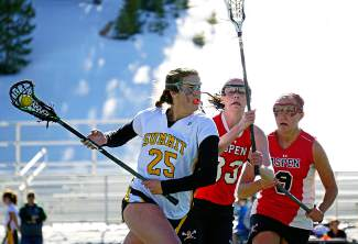 Weave through the masses: Summit lax captain Loren Keen (25) jukes past Aspen defenders to find a shot on goal late in a home varsity game last week, shot by @louietraub