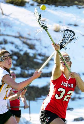 Summit's Laurel Bonner (14) tries to steal a loose ball from Aspen's Julia Boronski during a girl's varsity lacrosse game at home on April 7. The Tigers lost, 2-18.