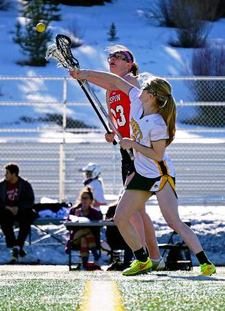 Clashing sticks: Summit's Kenady Nevicosi (13) faces off against Aspen's Claire Boronski during a home varsity lacrosse game in early April, caught by @louietraub
