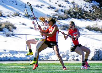 Summit's Kenady Nevicosi (13) is taken out of a play by an Aspen defender during a girl's varsity lacrosse game on April 7. The Tigers 2-18 loss.