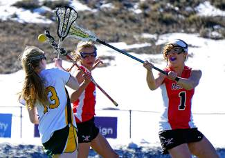 Summit attacker Kenady Nevicosi (13) tries to weave past Aspen defenders in a girl's varsity lacrosse game on April 7. Nevicosi had one goal in the Tigers 2-18.